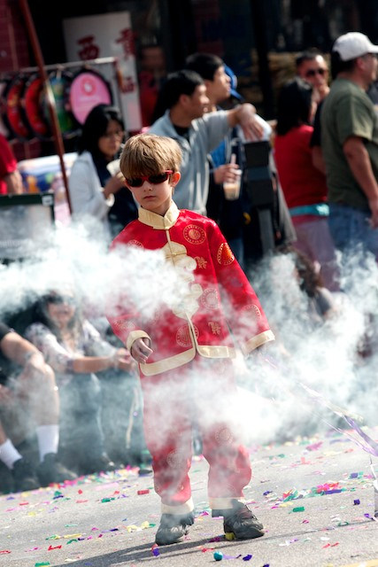 In the minutes leading up to the parade, kids play in the street chasing smoke bombs or streamers shot from cardboard canons.