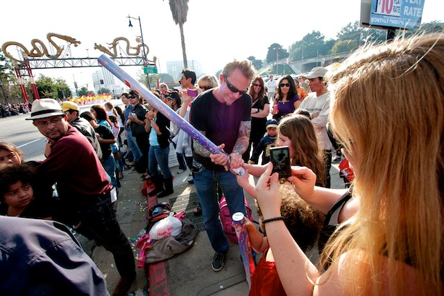 A man helps a young girl fire her cardboard canon as the parade goes by.