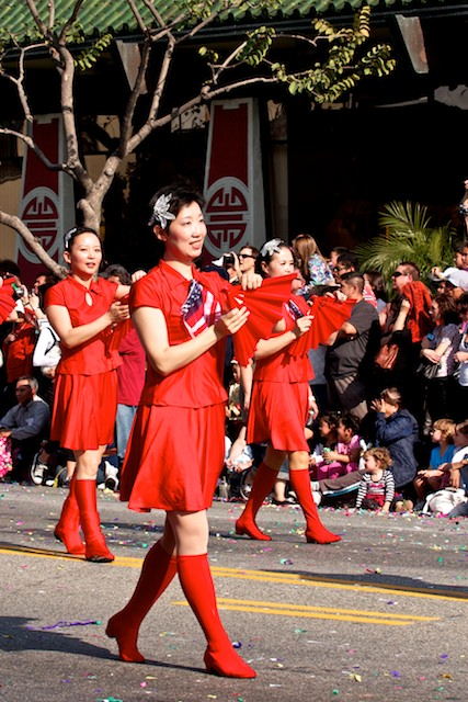 Women in red dresses perform a fan dance as they march in the 2011 Golden Dragon Chinese New Year Parade.