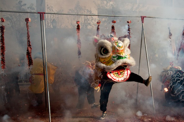 A Chinese lion dances through firecrackers in an attempt to ward off evil during the 2011 Golden Dragon Chinese New Year Parade.