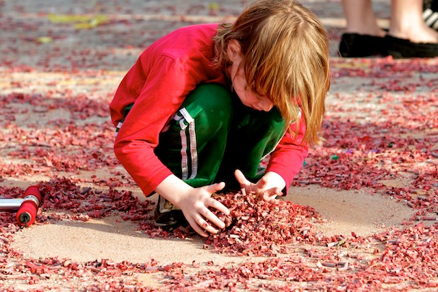 A child collects the paper casings of spent firecrackers after the closing ceremony of the 2011 Golden Dragon Chinese New Year Parade.