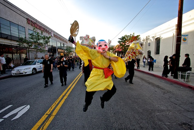 A man in a big head buddha costume leads a crowd down a street in Chinatown.