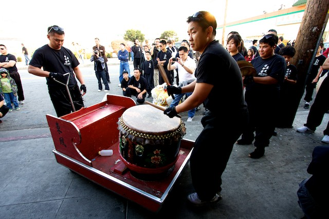 A man from the East Wind troupe plays the drum outside of a restaurant in Chinatown.