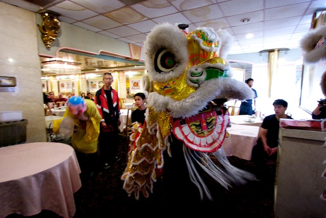A Chinese lion leaves a restaurant in Chinatown after chasing away evil spirits.